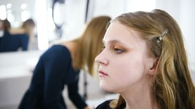 Jeune femme s'appliquant le maquillage au modèle dans le salon clips vidéos