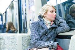 Jeune femme s'asseyant à l'intérieur d'un chariot de métro Images stock