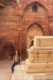 Jeune femme s'asseyant à l'intérieur du complexe de Qutub Minar, Delhi Image stock