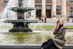 Jeune femme s'asseyant à la fontaine de parc utilisant le smartphone photographie stock