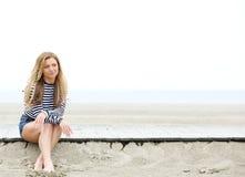 Jeune femme s'asseyant à la pensée de plage Photographie stock