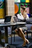 Jeune femme s'asseyant à la table avec l'ordinateur portable photo libre de droits