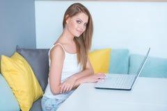 Jeune femme s'asseyant à la table avec l'ordinateur portable Photo stock
