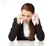 Jeune femme s'asseyant à un bureau, avec la grimace de la colère Photo stock