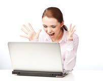 Jeune femme s'asseyant à un ordinateur portable, criant Photographie stock