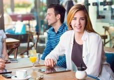 Jeune femme s'asseyant à une table avec ses amis Photographie stock