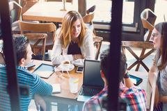 Jeune femme s'asseyant à une table avec ses amis dans un café Image libre de droits
