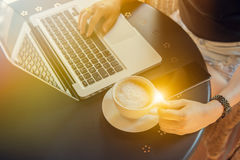 Jeune femme s'asseyant au bureau avec l'ordinateur portable Photographie stock libre de droits