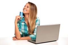 Jeune femme s'asseyant au bureau faisant des emplettes en ligne Photo stock