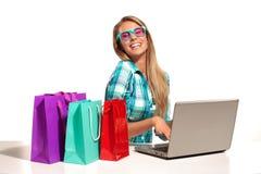 Jeune femme s'asseyant au bureau faisant des emplettes en ligne Images stock