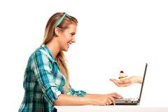 Jeune femme s'asseyant au bureau faisant des emplettes en ligne Image libre de droits