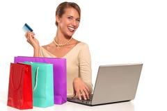 Jeune femme s'asseyant au bureau faisant des emplettes en ligne Image stock