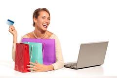 Jeune femme s'asseyant au bureau faisant des emplettes en ligne Images libres de droits