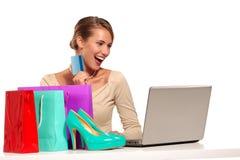 Jeune femme s'asseyant au bureau faisant des emplettes en ligne Photos libres de droits