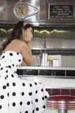 Jeune femme s'asseyant au compteur de wagon-restaurant photographie stock