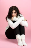 Jeune femme s'asseyant au-dessus du rose Photographie stock