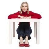 Jeune femme s'asseyant au petit bureau drôle Images libres de droits