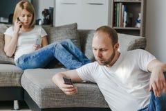 Jeune femme s'asseyant au sofa parlant au téléphone tandis que son mari utilise son téléphone portable dans leur salon Photographie stock