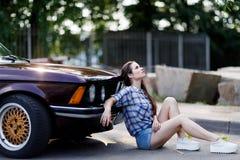 Jeune femme s'asseyant au sol à côté de la voiture Photo stock