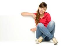 Jeune femme s'asseyant avec l'affiche blanc Images stock