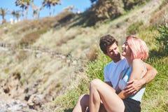 Jeune femme s'asseyant avec l'ami en dehors de rire Photos stock