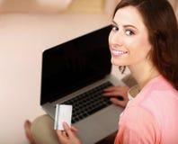 Jeune femme s'asseyant avec l'ordinateur portable et tenant le crédit Photo libre de droits