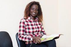 Jeune femme s'asseyant avec la magazine à disposition Photographie stock libre de droits