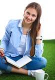 Jeune femme s'asseyant avec le livre sur l'herbe Photo libre de droits