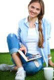 Jeune femme s'asseyant avec le livre sur l'herbe Images libres de droits
