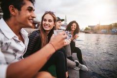 Jeune femme s'asseyant avec ses amis ayant des boissons Photo stock