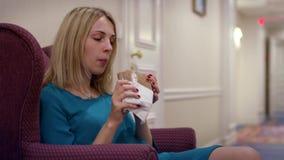 Jeune femme s'asseyant dans la chaise et mangeant le sandwich pendant le déjeuner banque de vidéos