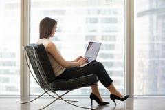 Jeune femme s'asseyant dans la chaise utilisant l'ordinateur portable pour étudier en ligne photographie stock libre de droits