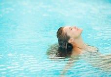 Jeune femme s'asseyant dans la piscine et la détente Photo libre de droits