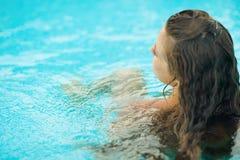 Jeune femme s'asseyant dans la piscine. vue arrière Images libres de droits