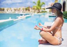 Jeune femme s'asseyant dans la pose de lotus par la piscine Image stock