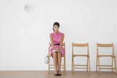 Jeune femme s'asseyant dans la salle d'attente Photo stock