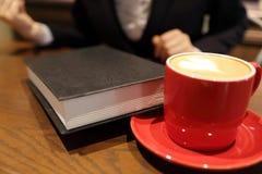 Jeune femme s'asseyant dans le café à la table en bois, au café potable et au livre lu Photos libres de droits