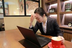 Jeune femme s'asseyant dans le café à la table en bois, au café potable et à la pensée soucieuse Sur la table est l'ordinateur po Photo stock