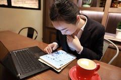 Jeune femme s'asseyant dans le café à la table en bois, café potable et à l'aide de la protection Sur la table est l'ordinateur p Photo libre de droits