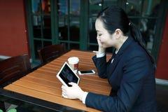 Jeune femme s'asseyant dans le café à la table en bois, café potable et à l'aide de la protection Sur la table est l'ordinateur p Image libre de droits