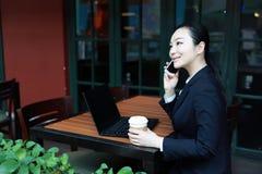 Jeune femme s'asseyant dans le café à la table en bois, café potable et à l'aide du smartphone Sur la table est l'ordinateur port Photos stock