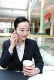 Jeune femme s'asseyant dans le café à la table en bois, café potable et à l'aide du smartphone Sur la table est l'ordinateur port Photos libres de droits