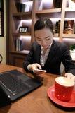 Jeune femme s'asseyant dans le café à la table en bois, café potable et à l'aide du smartphone Sur la table est l'ordinateur port Photographie stock libre de droits