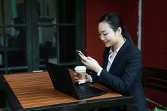 Jeune femme s'asseyant dans le café à la table en bois, café potable et à l'aide du smartphone Sur la table est l'ordinateur port Image stock