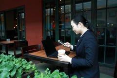 Jeune femme s'asseyant dans le café à la table en bois, café potable et à l'aide du smartphone Sur la table est l'ordinateur port Photo stock