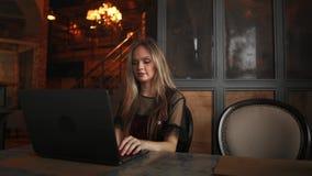 Jeune femme s'asseyant dans le café à la table en bois, café potable et à l'aide du smartphone Sur la table est l'ordinateur port banque de vidéos