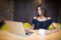 Jeune femme s'asseyant dans le café à la table en bois, café potable et à l'aide du smartphone Sur la table est l'ordinateur port Images libres de droits