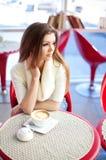 Jeune femme s'asseyant dans le café avec une cuvette de thé photographie stock libre de droits