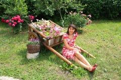 Jeune femme s'asseyant dans le jardin Photo libre de droits