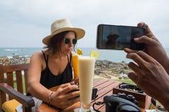 Jeune femme s'asseyant dans le jus potable de restaurant et le repas de attente Images libres de droits